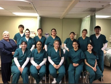 Health Leadership High School students wearing scrubs in a medical care facility